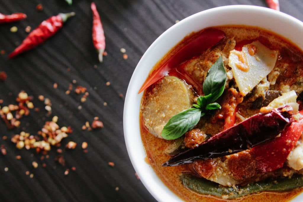 Make an authentic Thai red curry. Bowl of food containing red and green peppers, potatoes, red-coloured sauce and some peppermint leaves.
