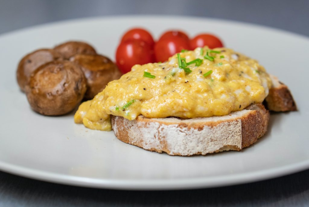Make scrambled eggs. Plate with toast covered with scrambled eggs, cherry tomatoes and baked potatoes