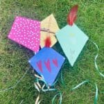 Four colourful micro kites laying on the grass.