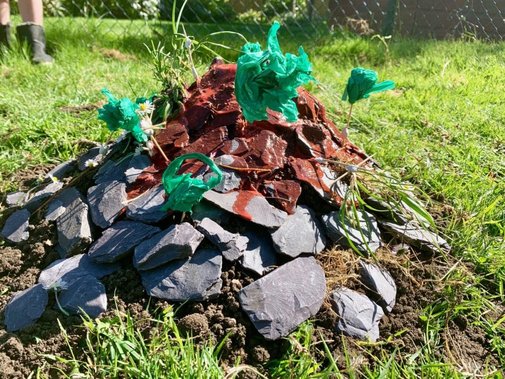learn how to make a simple volcano that erupts - image of homemade volcano science experiment in garden.