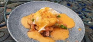 Poached egg and Hollandaise sauce - photo of eggs and hollandaise on a blue plate