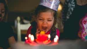 childrens virtual birthday party - child blowing out candles on birthday cake