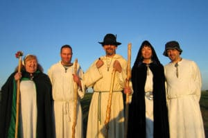 Modern day druids - women and men in druid robes in the sunlight.