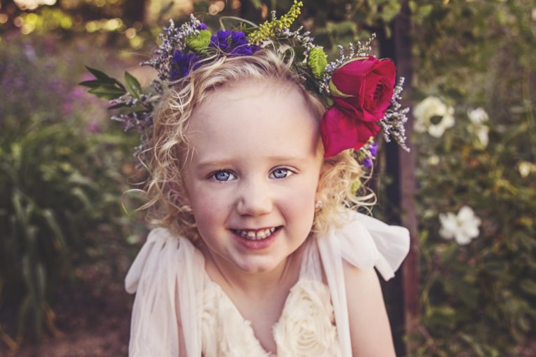 Make a flower crown - young blonde haired girl in red flower crown outdoors in Summer