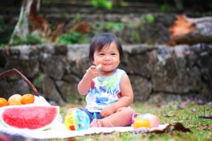 summer solstice food and drink ideas - toddler sitting on a picnic mat surrounded by summer food outdoors.