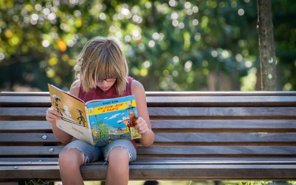 Discover Asterix and Obelix - image of a child reading an Asterix and Obelix comic book on a park bench.