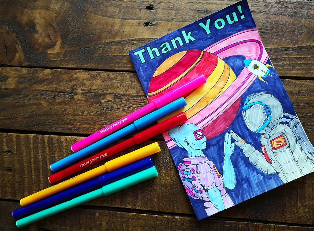 Thank you cards for kids to make - handmade thank you card, picture of an alien and spaceman high fiving, with coloured pens.
