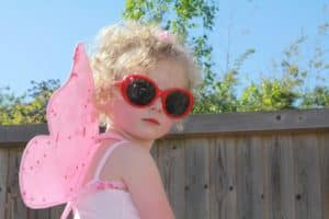cardboard fairy wings- picture of little girl wearing pink fairy wings, pink dress and red sunglasses.